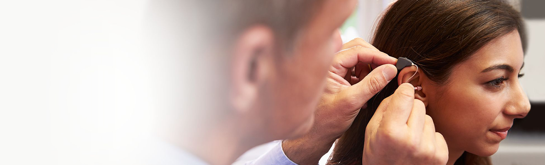 doctor placing hearing aid in woman's ear